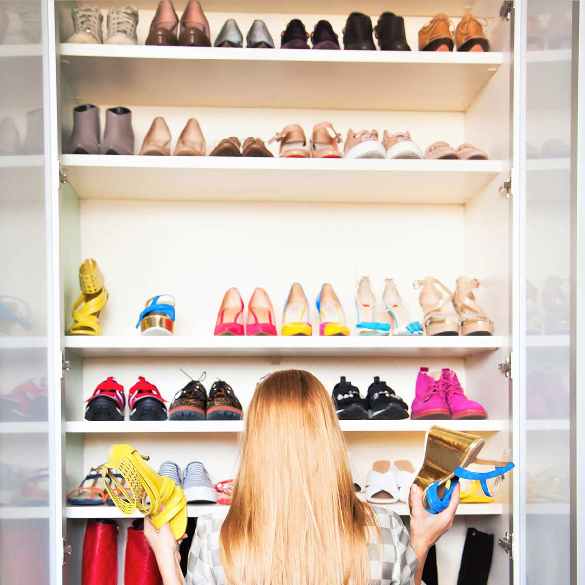 Woman with long blond hair holding a shoe in each hand while standing in front of shoe closet and trying to declutter shoes.