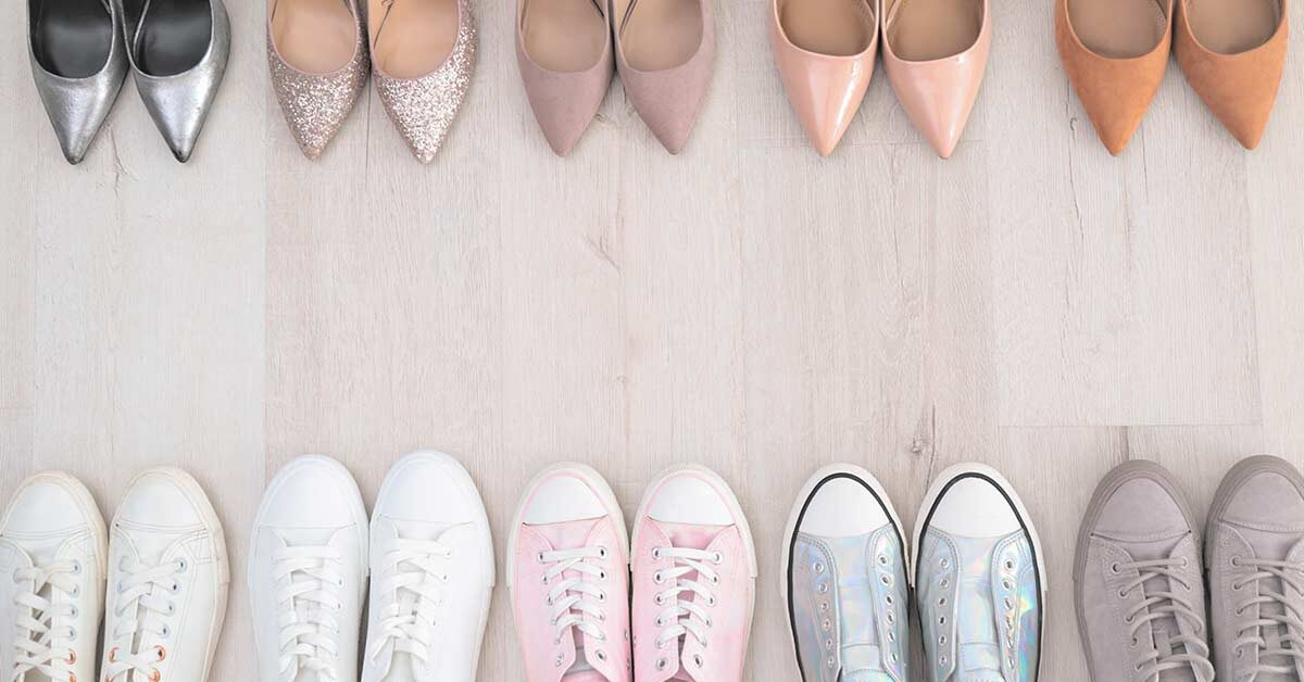 Several pairs of shoes lined up on wood floor with heels at top and sneakers at the bottom.