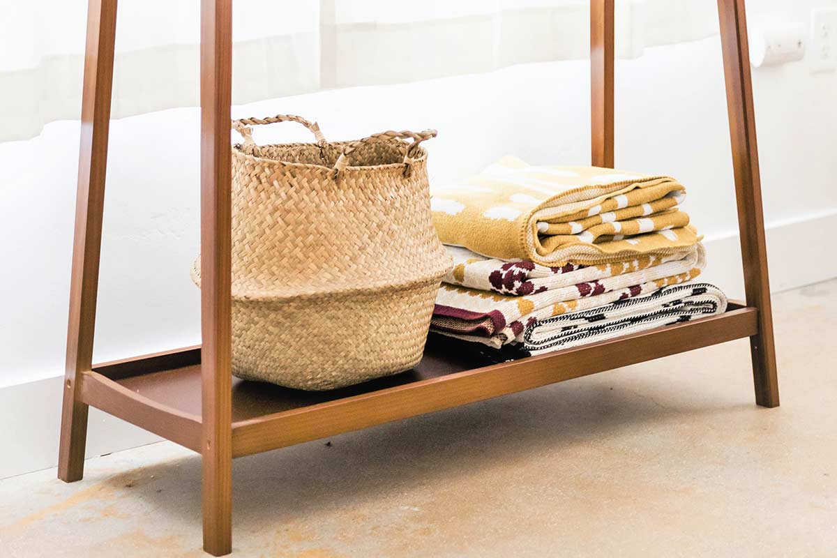 Wood shelf on bottom of table with woven basket and small stack of neatly folded blankets against white wall.