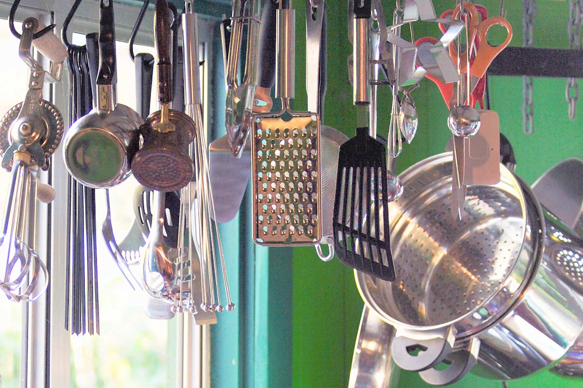 Kitchen pots and utensils hanging from hooks with green walls and window in background.