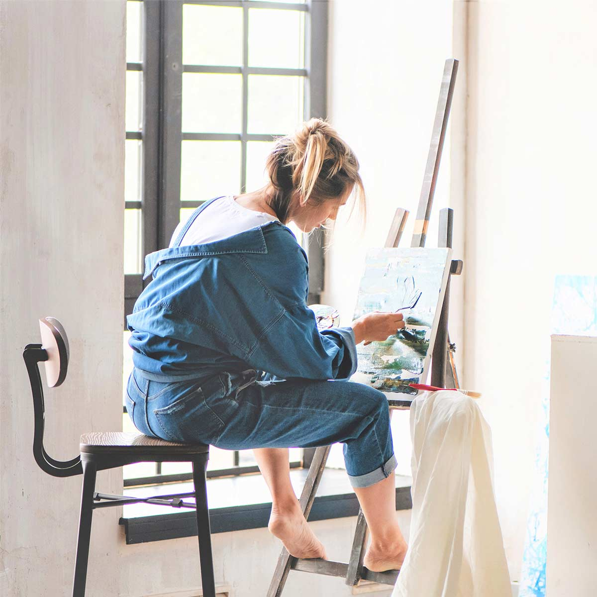 Blonde woman in denim clothing painting in sunny home studio.