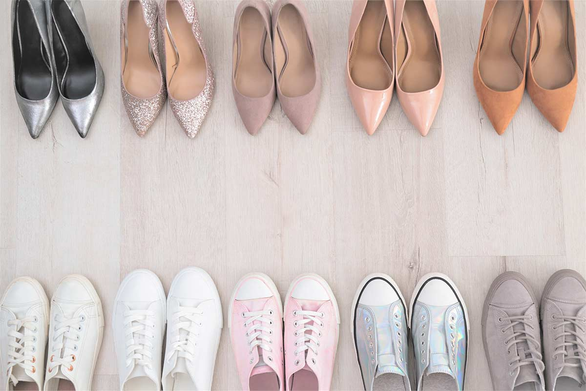 Several pairs of decluttered shoes lined up on wood floor with heels at top and sneakers at the bottom.