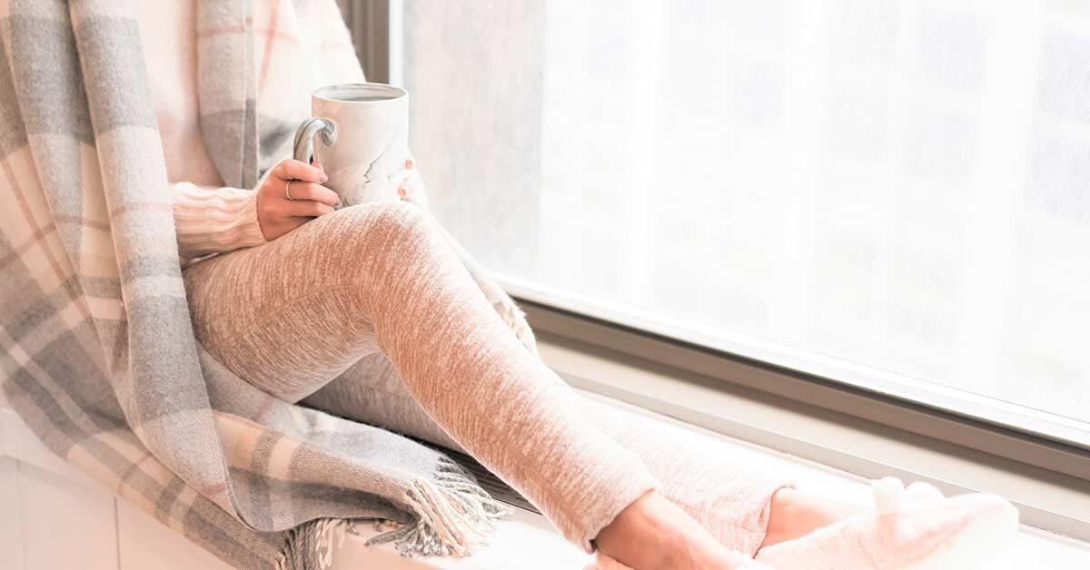 Woman wearing cozy clothes, slippers, and blanket while holding coffee mug and relaxing next to window during winter break.