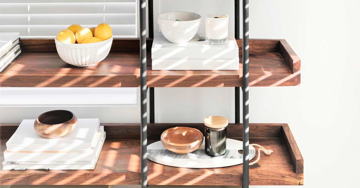 Carefully chosen white and neutral decor items on wood and iron shelves in front of white wall.