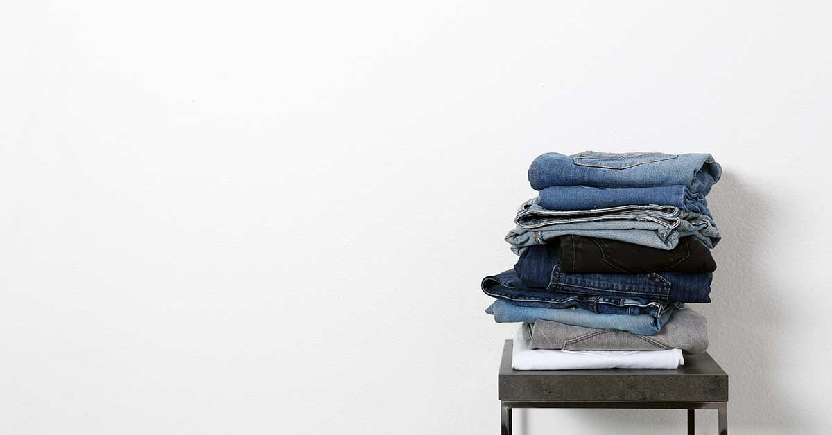 Pile of folded jeans on stool against white wall.