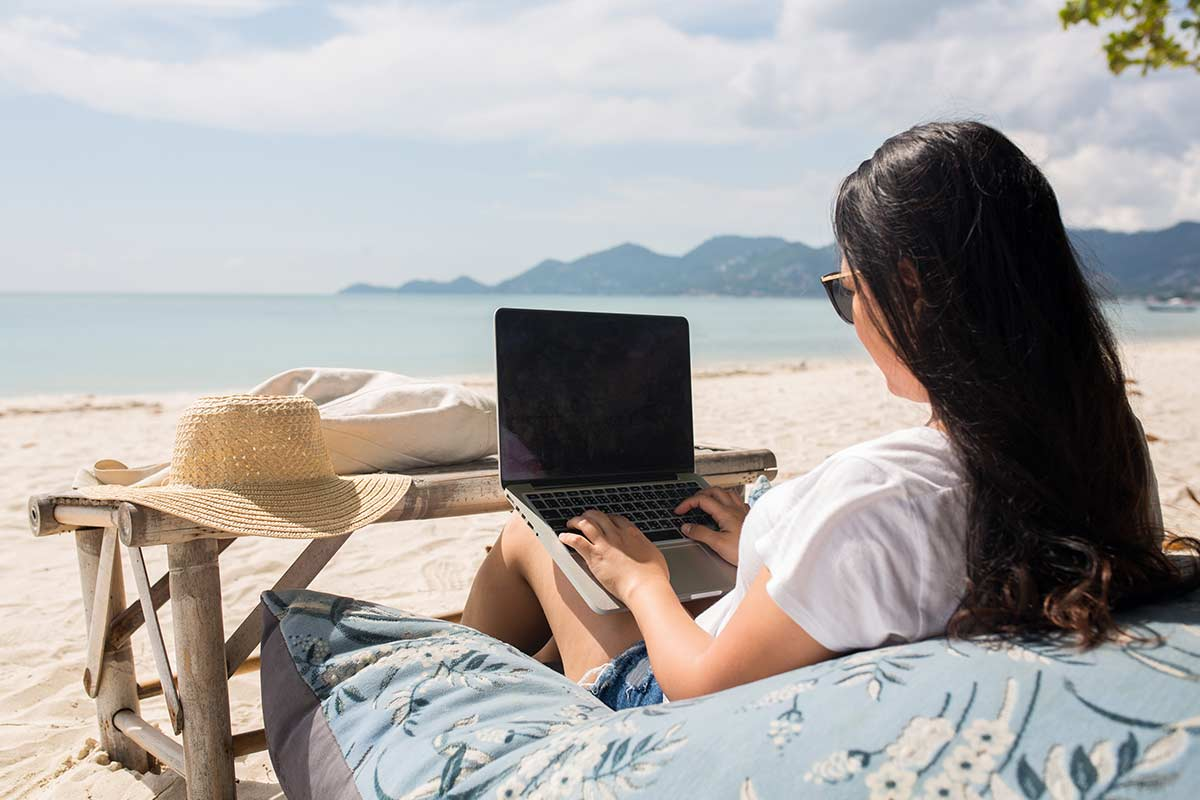 Woman with long black hair and white tee shirt sitting on huge pillow while being productive on her laptop at the beach.