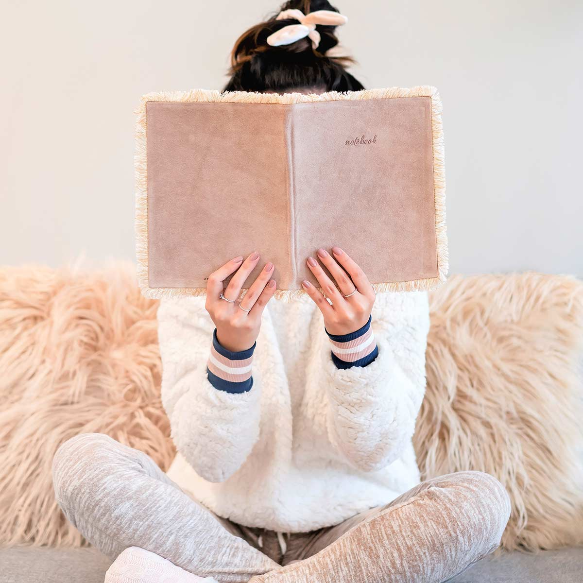 Woman sitting cross-legged on couch in front of fuzzy pillows and holding up old journal to read over winter break.