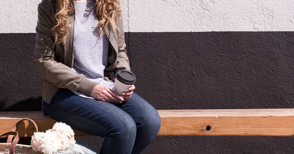 Woman in casual clothing sitting on wood bench outdoors while holding coffee cup and taking a break.