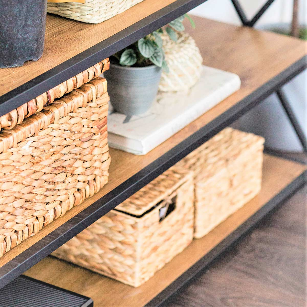 Plants and wicker baskets for storing clutter on wood shelves.
