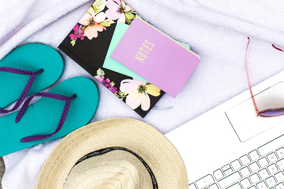 Items necessary to be productive during the summer at the pool - laptop, sunglasses, straw hat, flip-flops, planner, notebook.