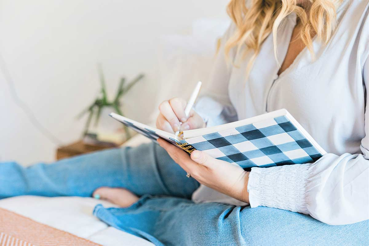 Woman with long blond hair wearing blue blouse and denim jeans sitting and writing about creative journal topics in black and white buffalo check journal.