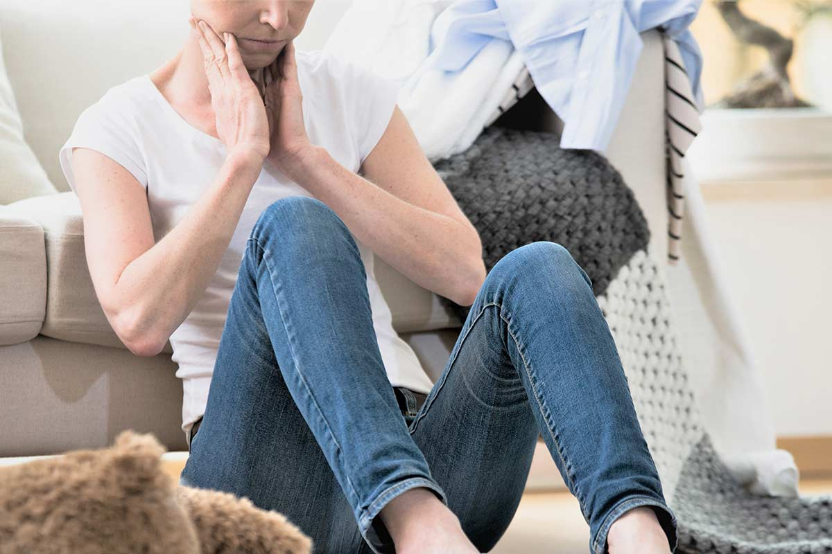 Woman sitting on floor feeling overwhelmed by cluttered house.