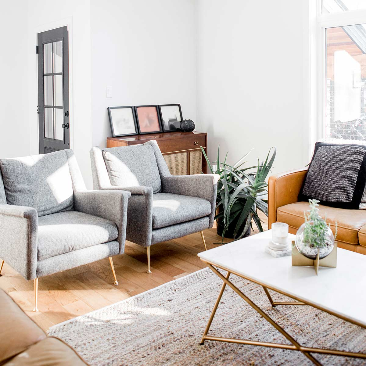 Simple white living room with grey and leather furniture.