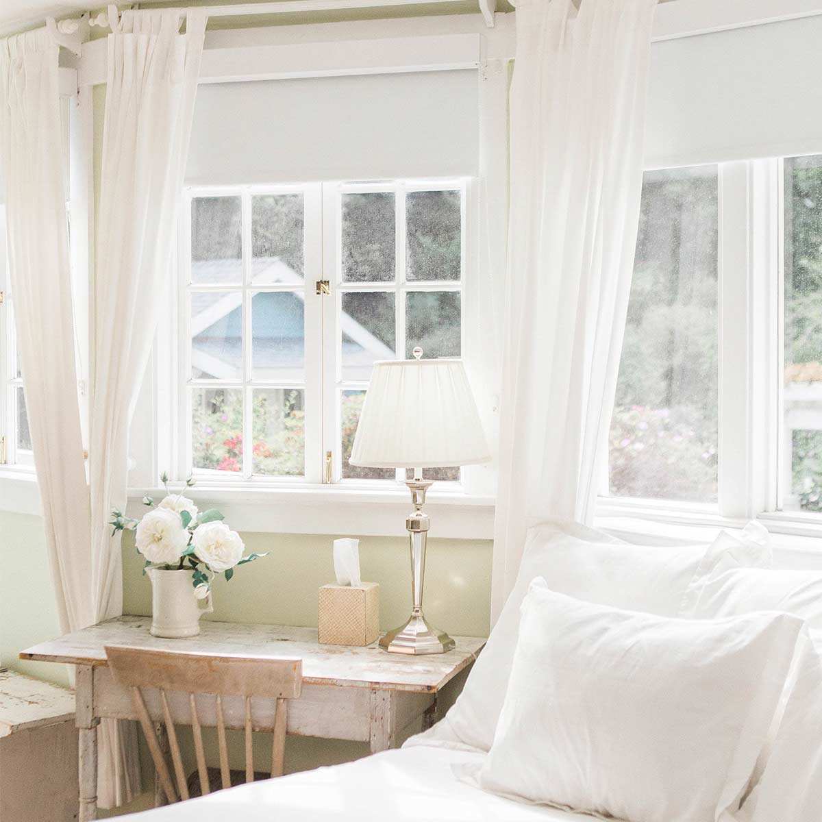 Clutter-free bright and airy bedroom with white linens and rustic desk.