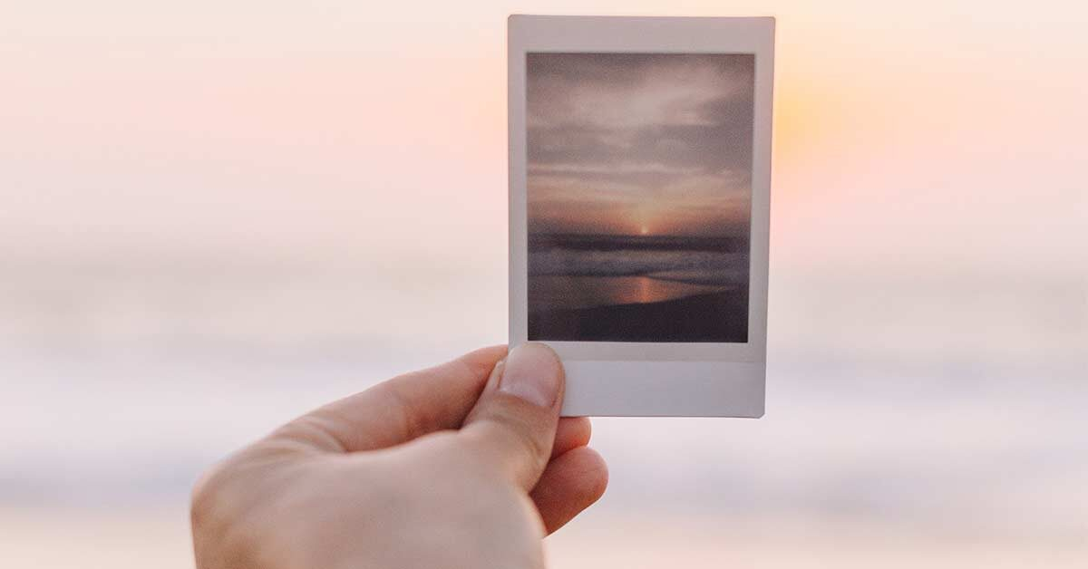 Hand holding up picture of sunset to compare with real sunset.