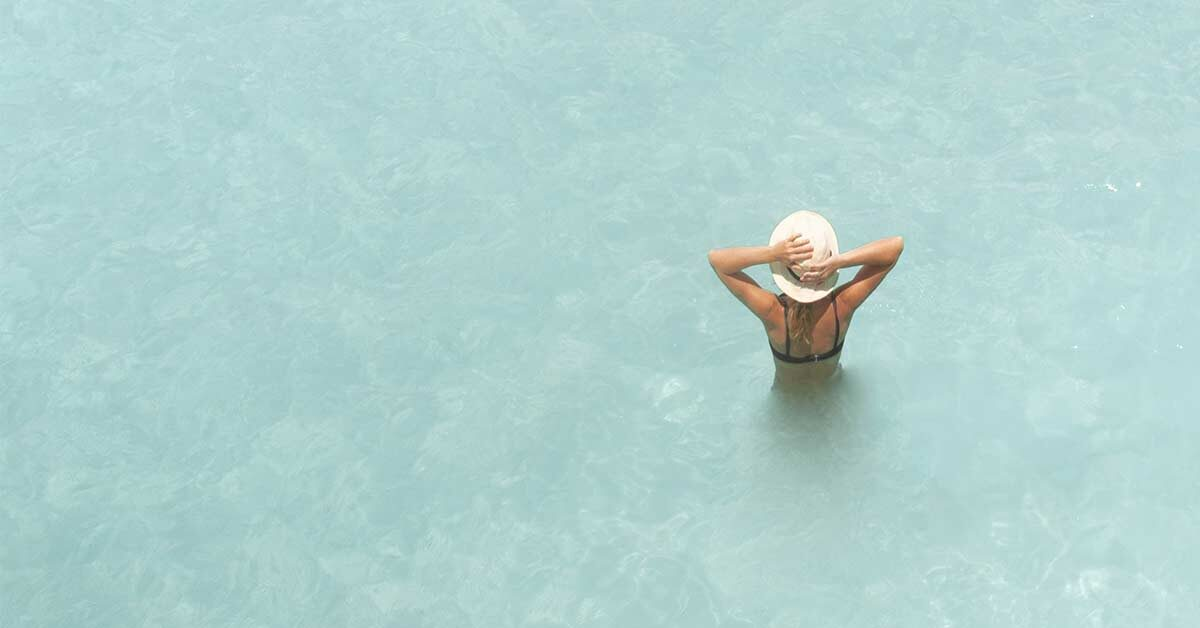 Woman standing in light turquoise water on a sunny day.