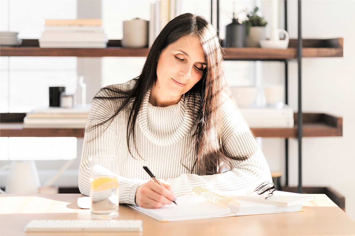Woman in white sweater with long dark hair doing morning creative writing while sitting at table in sunny room.