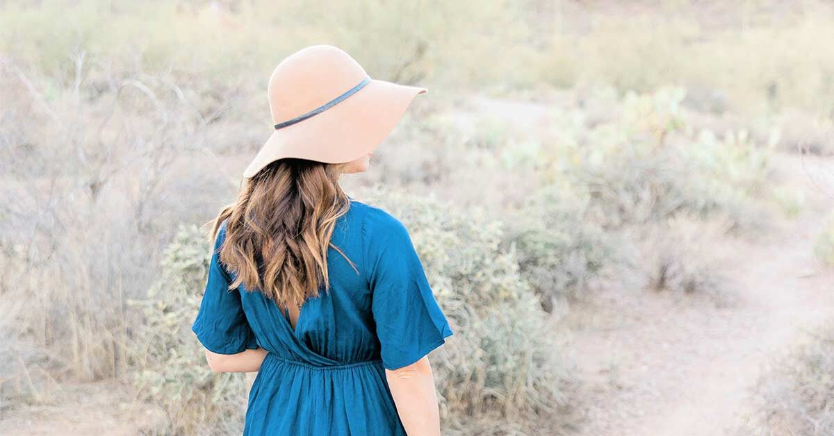 Woman with long hair wearing a floppy hat and blue dress standing in the desert on a slow down Sunday.