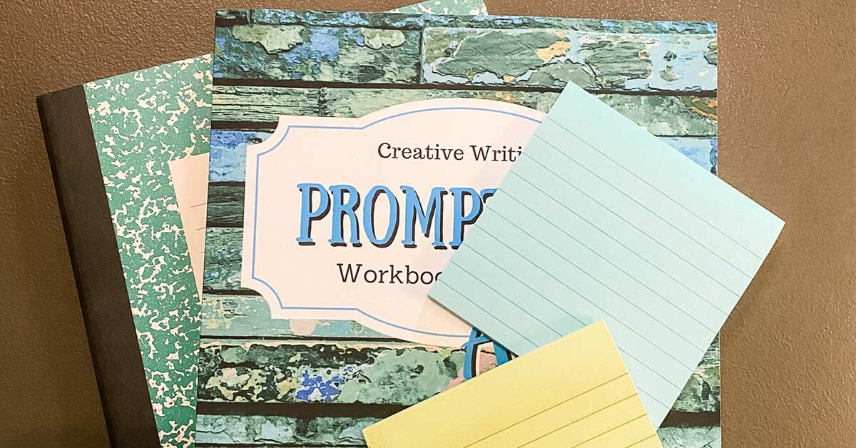 Creative writing journal, notebook, and sticky notes on brown table.