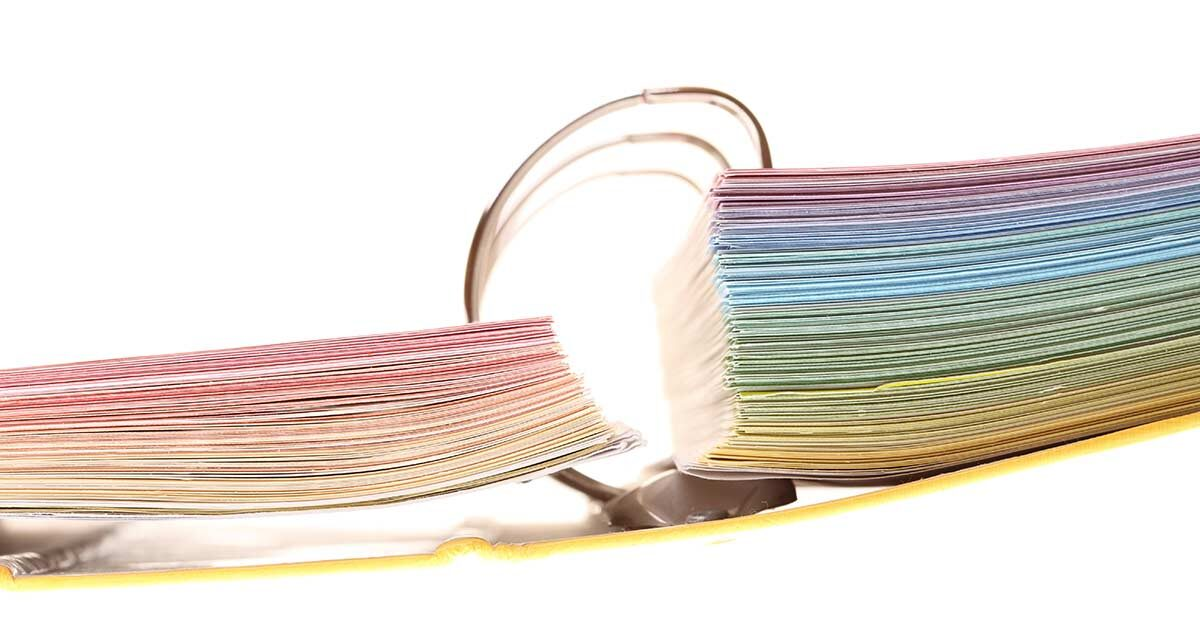 End view of open 3 ring binder with colorful pages on white background.