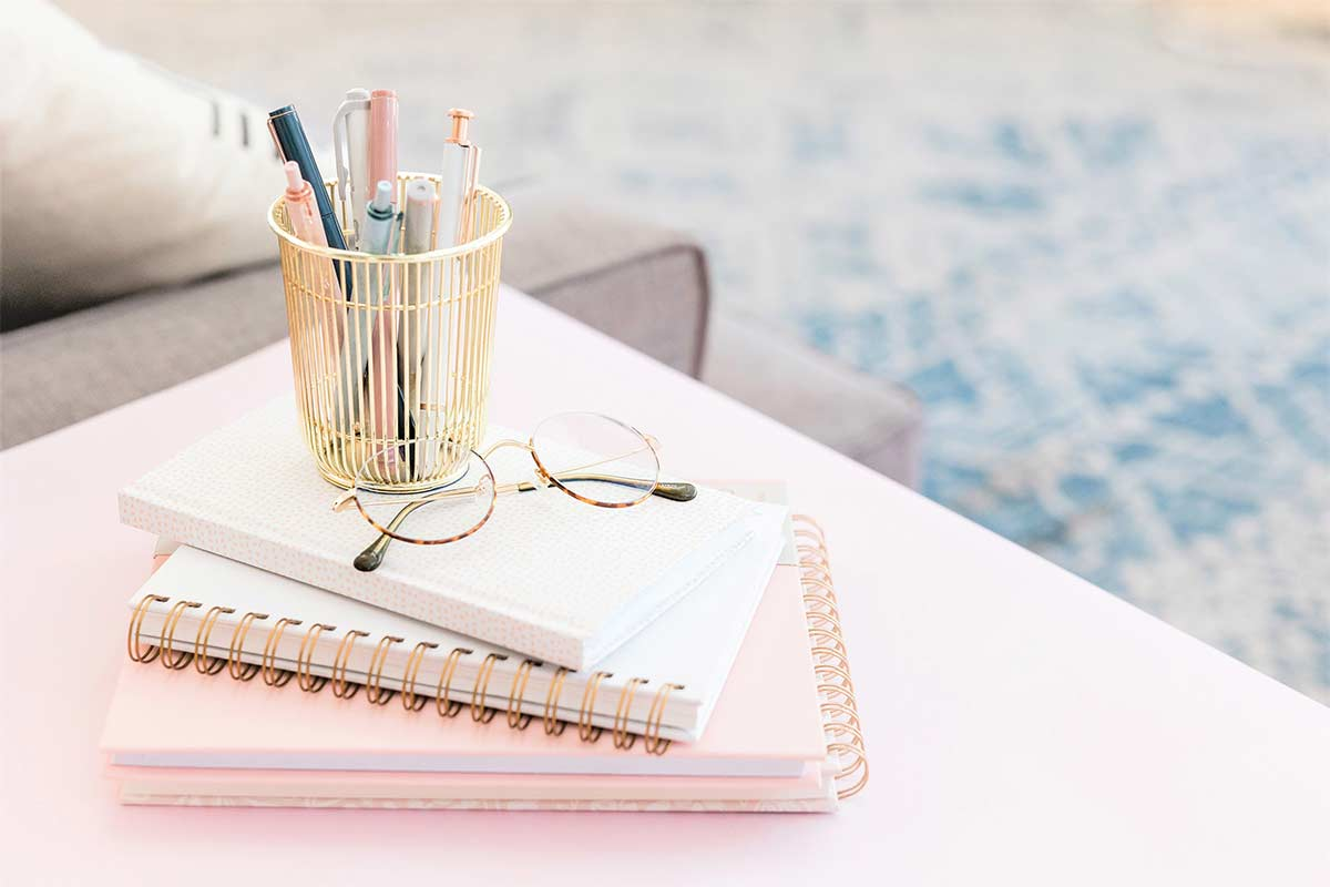 Pink-tinted table and journal stack with glasses and gold-tone pen holder.
