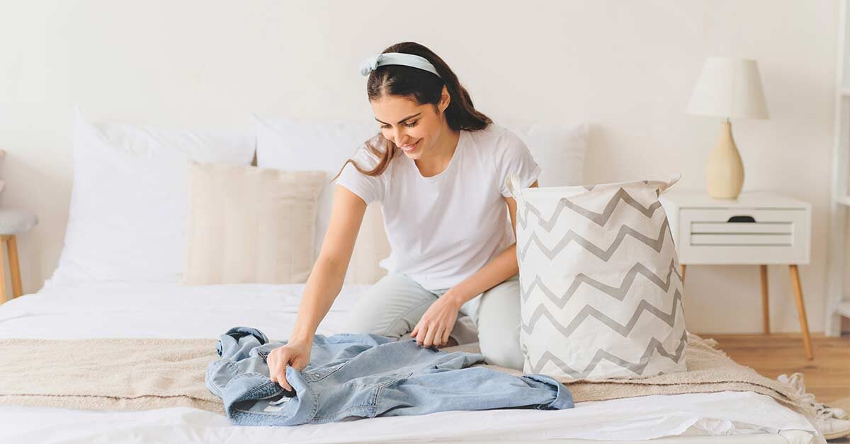 Woman sitting on bed decluttering items and preparing donation bag.