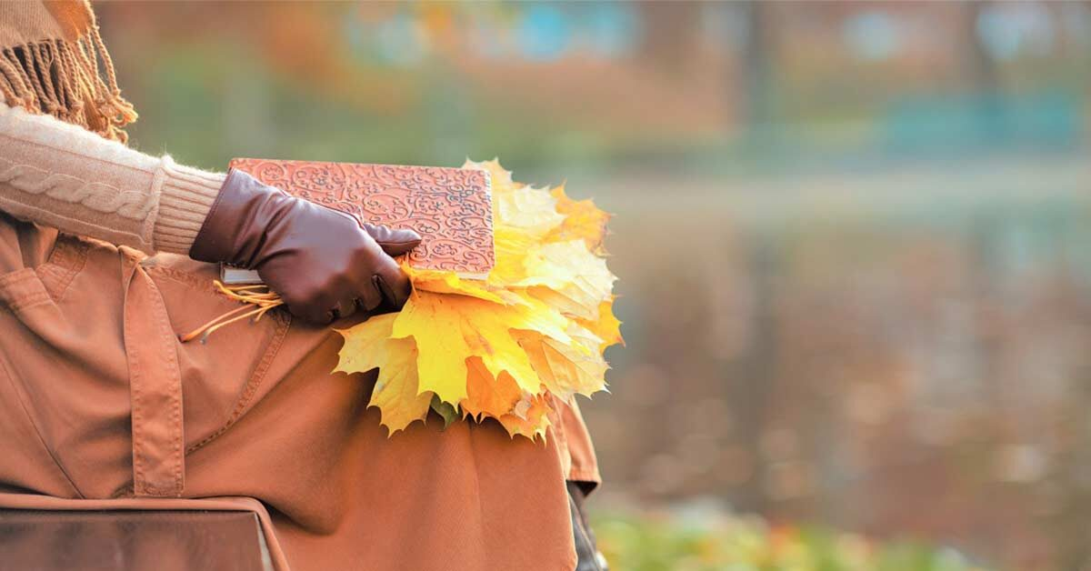 Woman in fall clothing and gloves sitting on bench and holding yellow leaves and notebook for writing fall journal prompts.