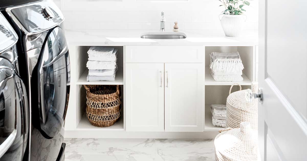 Beautiful white laundry room with black washer and dryer.