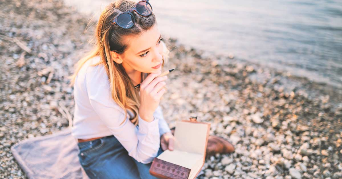 Woman with blond hair wearing blue shirt and jeans sitting on towel on stony beach while preparing to write responses to creative writing prompts for adults.