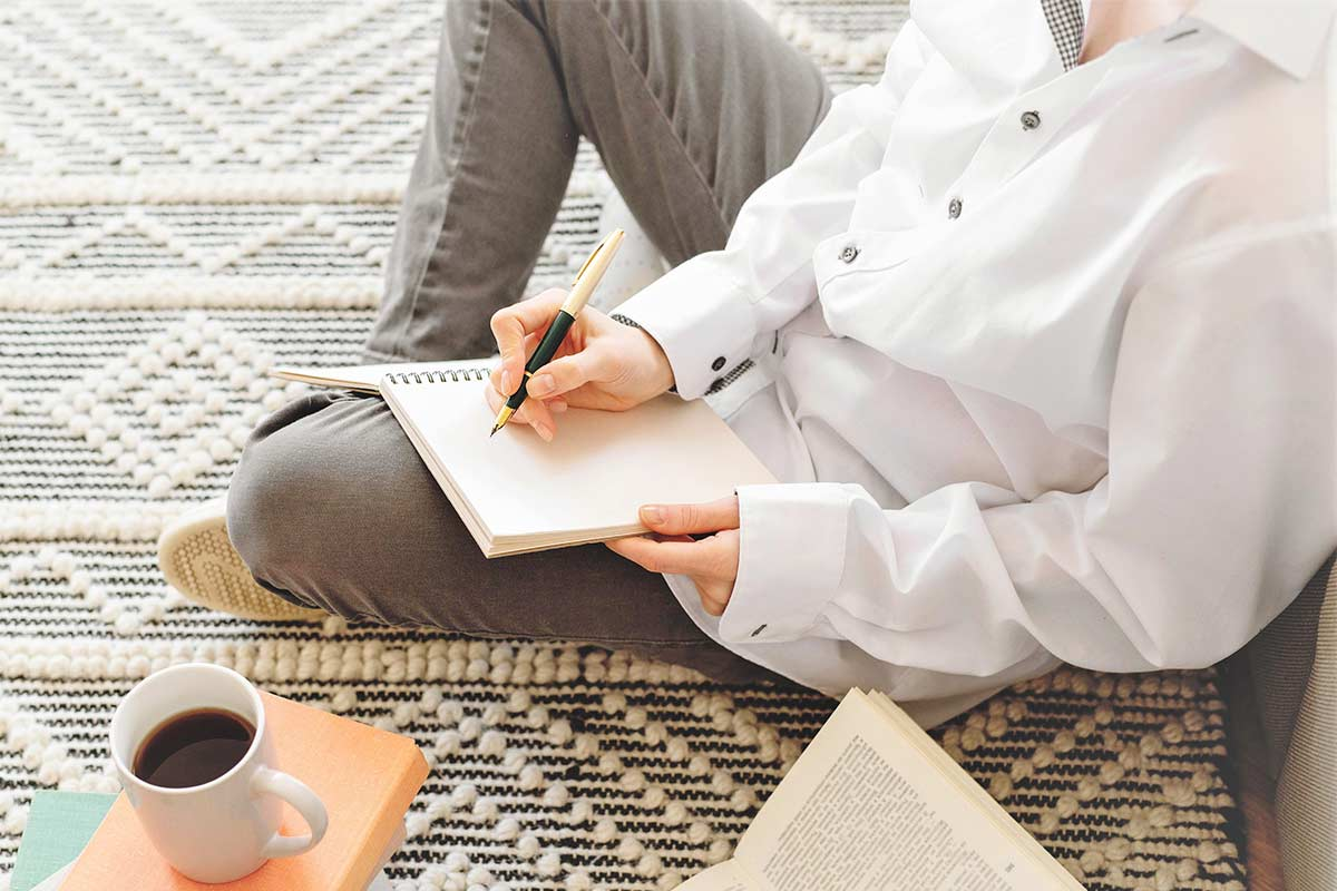 Woman in white shirt and black jeans sitting on floor with open notebook and preparing to use creative writing prompts.