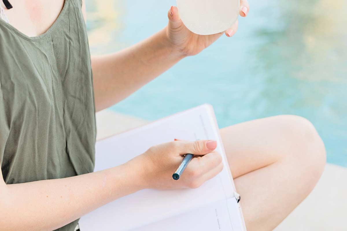 Woman in shorts and green tank top sitting by pool while writing in a daily journal.