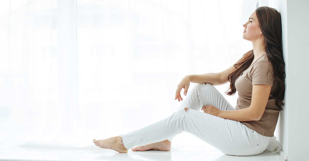 Woman with long dark hair wearing casual clothes and sitting on windowsill in white, clutter-free room.