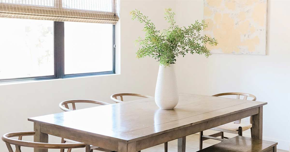 Clutter-free dining table with white vase and greenery in sunny white dining room.