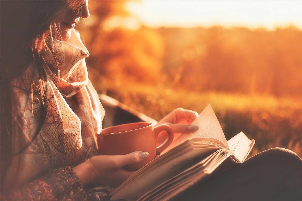 Woman in patterned scarf and sweater sitting in autumn sunlight while holding coffee mug and reading through a fall journal.