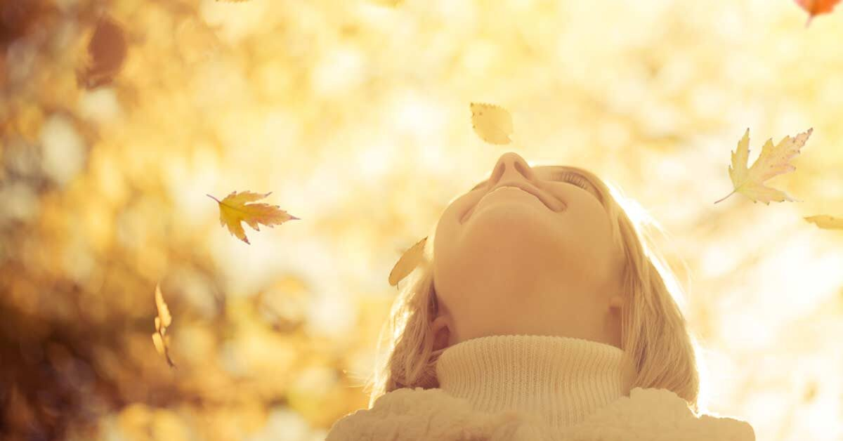 Blonde woman in turtleneck sweater smiling up at falling leaves on a sunny day.