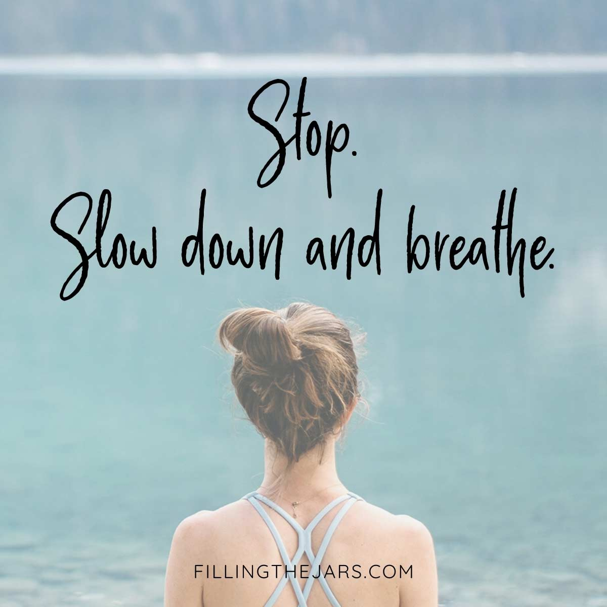 Slow down and breathe quote in black text on background of woman wearing yoga outfit with hair pulled up and looking at blue mountain lake.