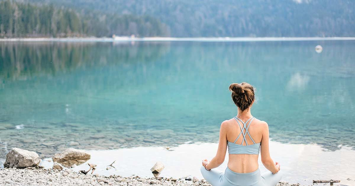 Woman wearing yoga outfit with hair pulled up sitting on stony beach taking time to slow down and breathe while looking at blue mountain lake.