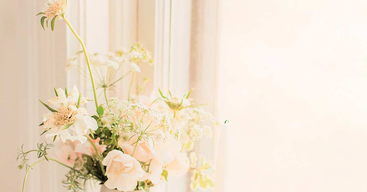Wildflowers in white vase on windowsill in morning sun.
