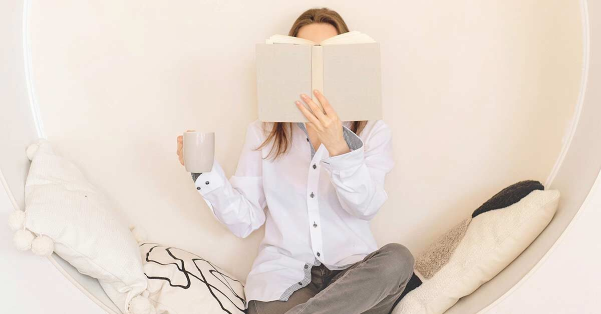 Woman taking it slow by sitting in circular seat while holding coffee mug and reading.