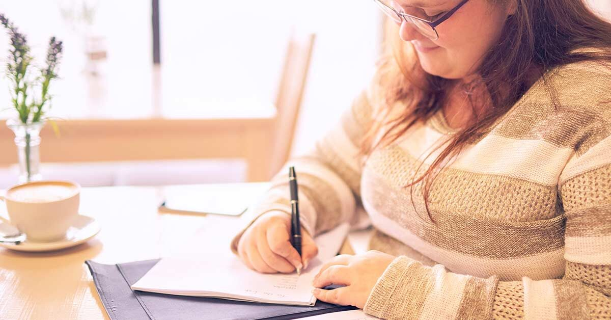 Woman with long dark hair wearing a sweater and glasses sitting at a table to do daily journal writing.