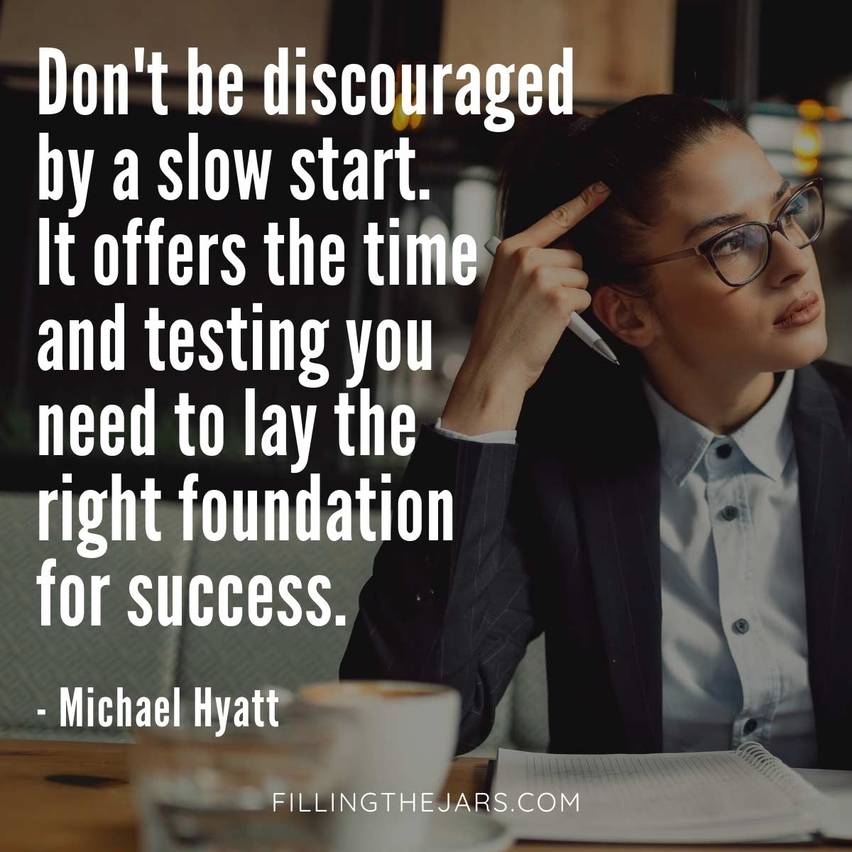 Michael Hyatt slow start quote in white text over background of young woman wearing glasses and business attire working at a cafe table.