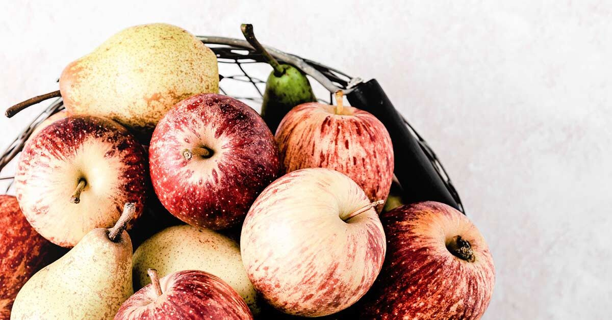 Top view of apples and pears in mesh bowl on white counter - perfect to welcome fall.