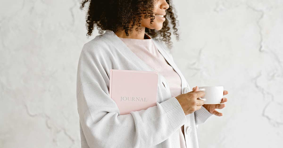 Woman in pink t-shirt and gray sweater holding pink journal and white coffee cup.