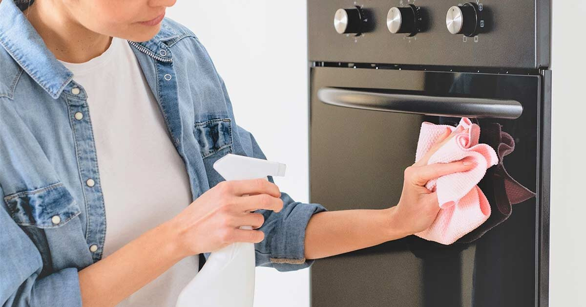 Woman wearing white t-shirt and denim shirt using spray cleaner to clean the front of her oven.