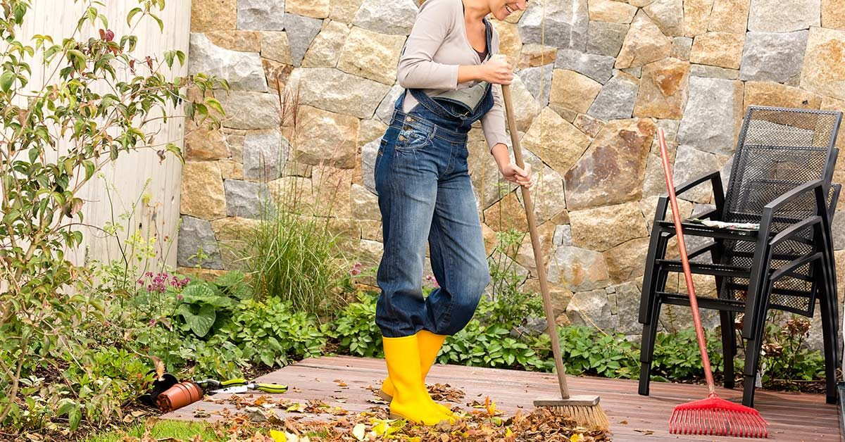 Woman wearing overalls and yellow boots sweeping deck as part of fall cleaning tasks.