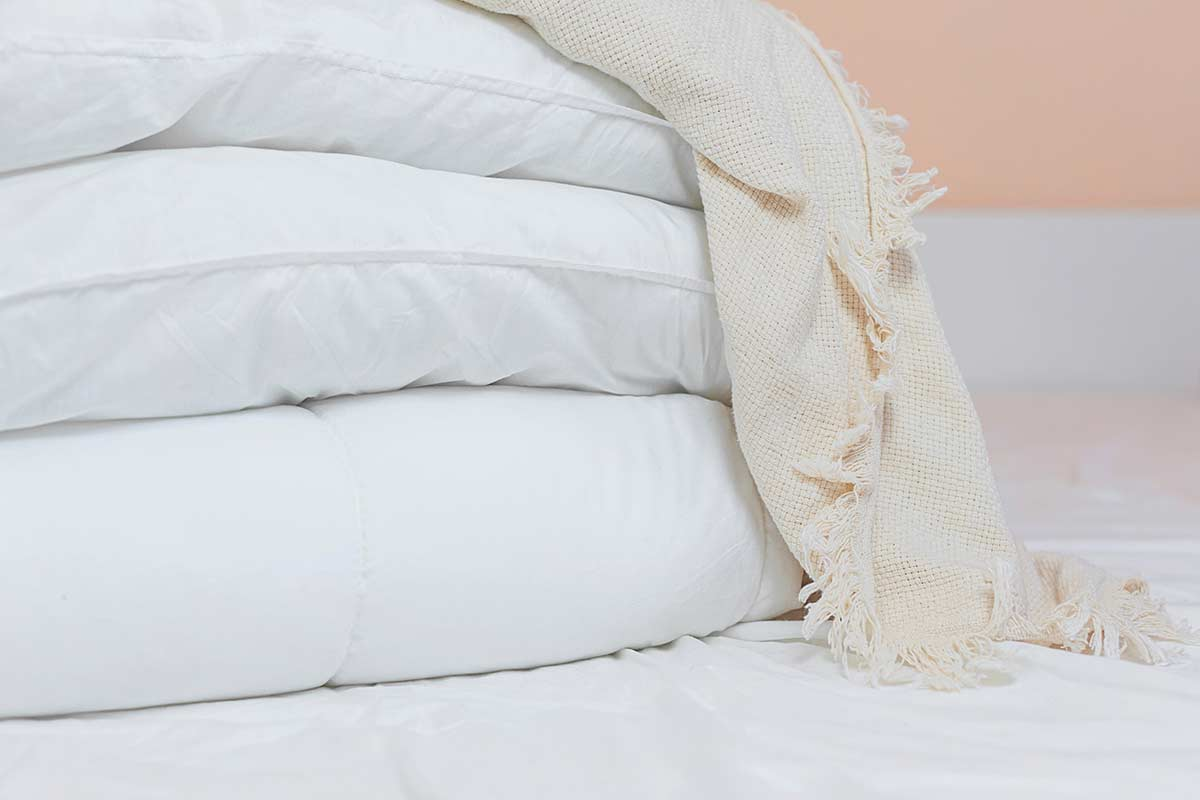 White pillows and bedding piled on bed after deep fall cleaning.