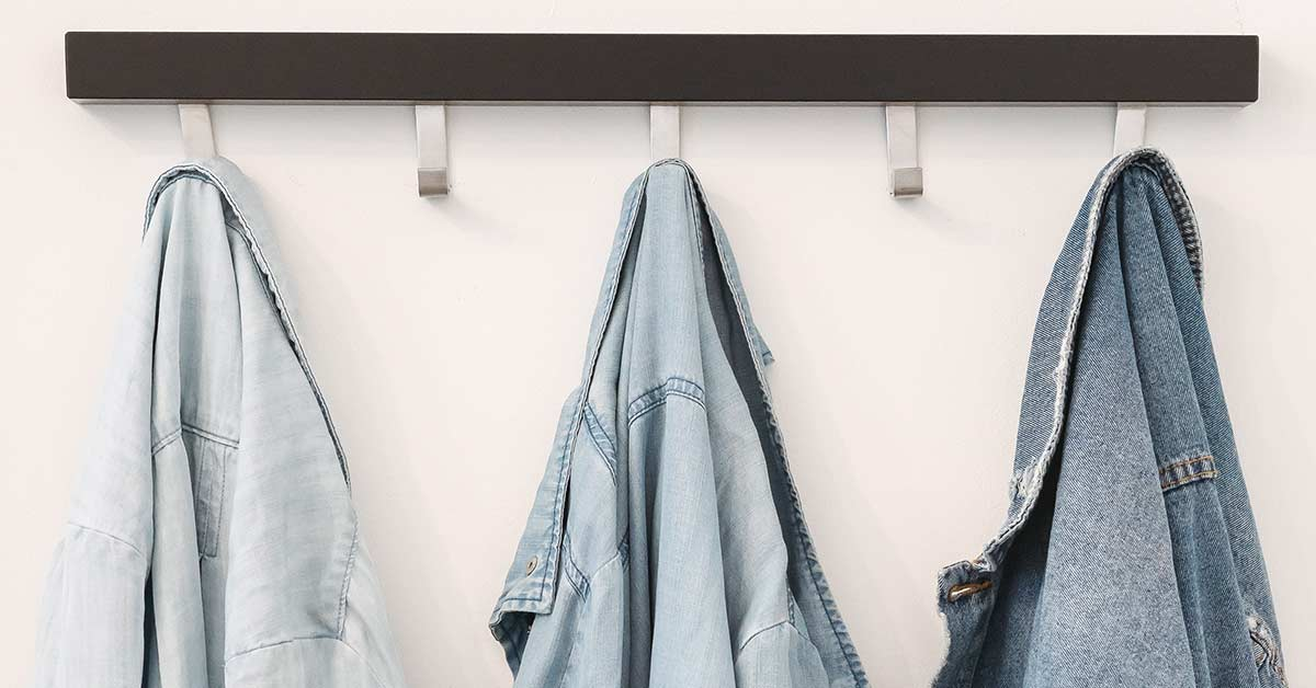 Denim shirts and jackets that need to be decluttered hanging on hooks against white wall.