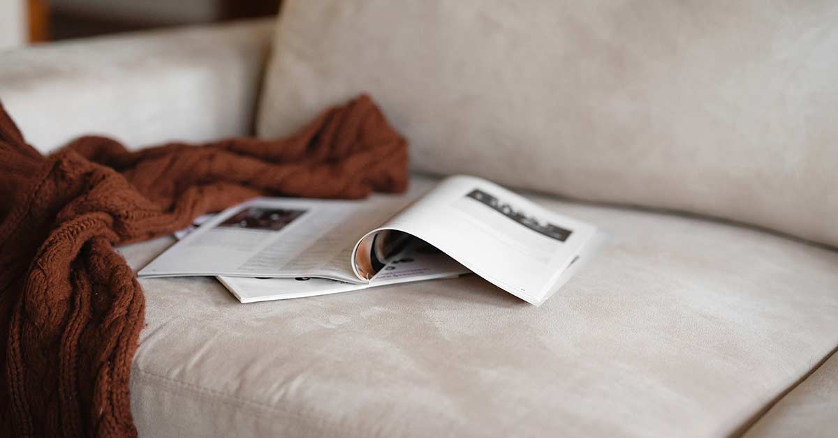 Open magazines and brown knit blanket left on white couch.