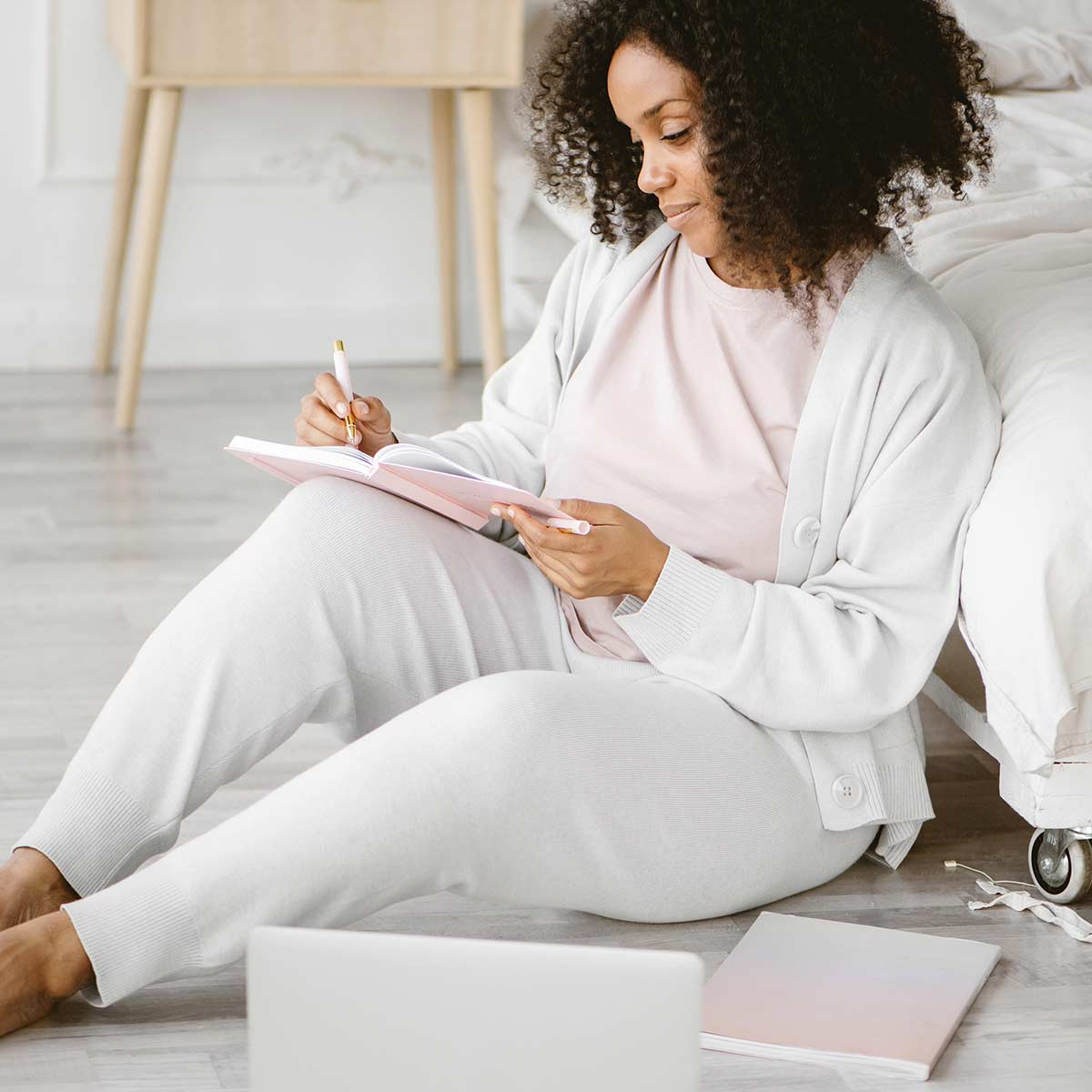Woman in pink t-shirt, gray sweater and leggings sitting on bedroom floor while writing calming journal prompts in pink journal.