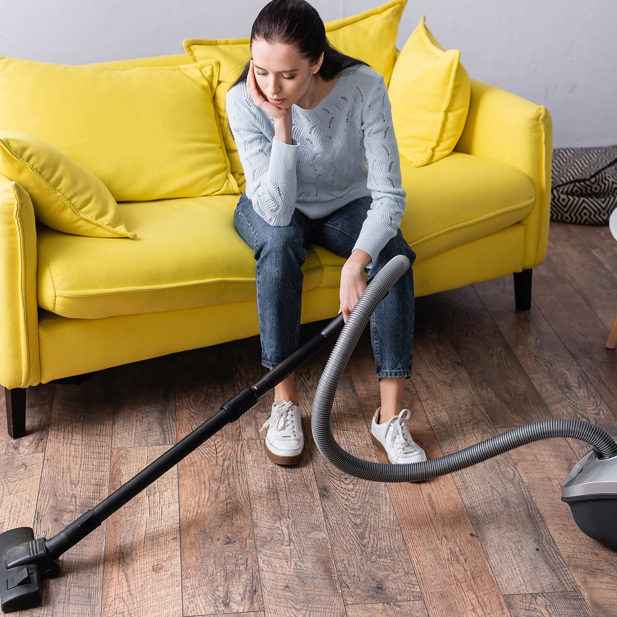 Woman with no energy to clean the house sitting on yellow couch holding part of vacuum.